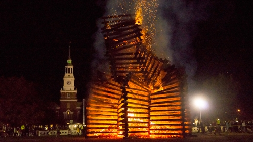 a bonfire burning with Baker Tower in the background