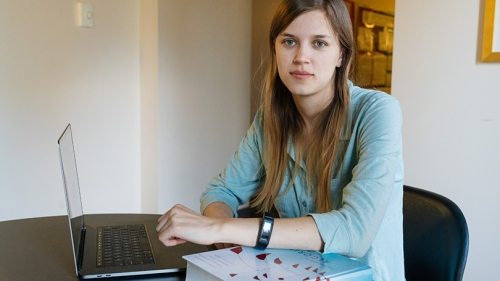 Margaret Lawson sitting at a table with her laptop and a copy of her mentor's textbook