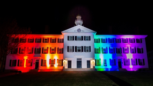 Dartmouth Hall lit up with red, orange, green, blue, and purple lights