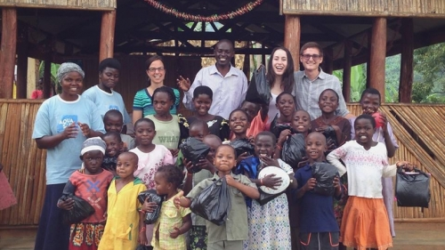 Sydney Kamen standing with a group of children in Uganda