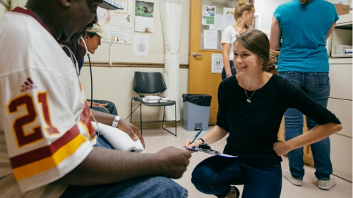 Public health intern Emma Hartswick '17 helps a client tend to an aching foot.